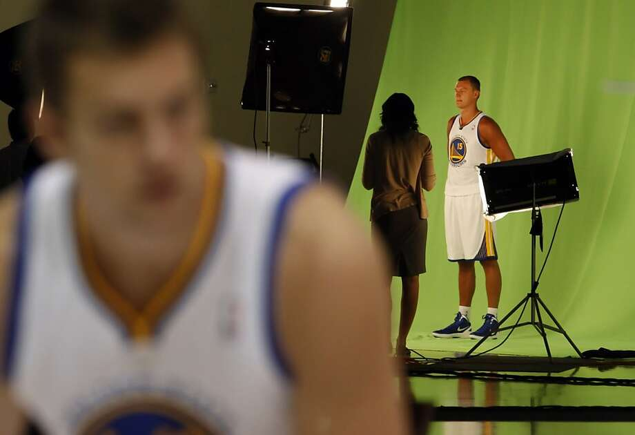 Andris Biedrins (rear) makes a promo video on a green screen as David Lee poses for a photograph. Photo: Carlos Avila Gonzalez, The Chronicle