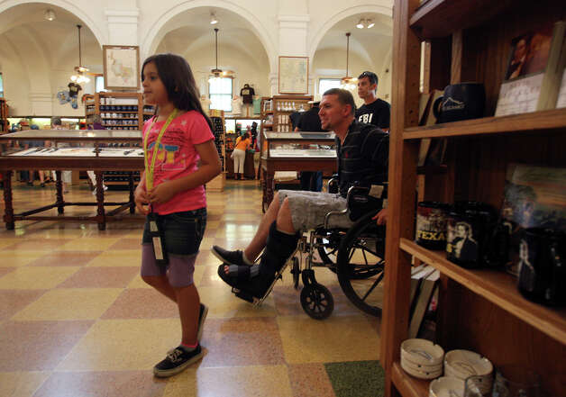 Mike Staublein, of Bakersfield, CA, and his daughter, Luciana, 8, shop at the Alamo gift shop, Monday, Oct. 1, 2012. Event Network, which manages gift shops at several historical sites nationally, has taken over the Alamo gift shop starting Monday. The General Land Office hired the firm. GLO took over the management of the Alamo from the Daughters of the Republic of Texas. Photo: Jerry Lara, San Antonio Express-News / © 2012 San Antonio Express-News