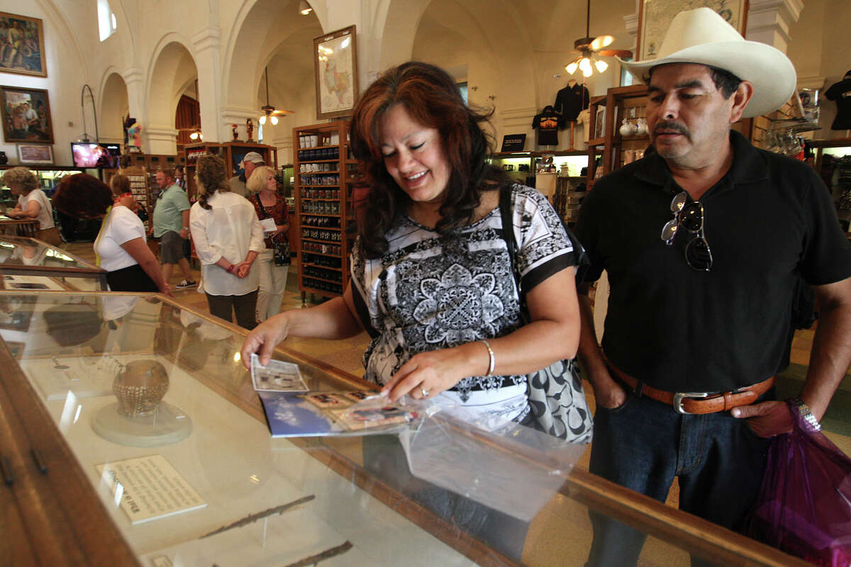 Maria Guevara mounts souvenir photos on an album while her husband, Jose, watches at the Alamo gift shop, Monday, Oct. 1, 2012. Event Network, which manages gift shops at several historical sites nationally, has taken over the Alamo gift shop starting Monday. The General Land Office hired the firm. GLO took over the management of the Alamo from the Daughters of the Republic of Texas. The couple is from Dallas