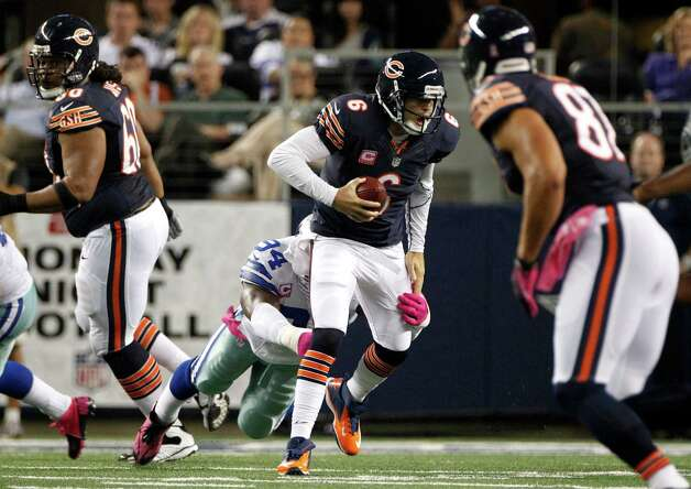 Chicago Bears' Jay Cutler (6) scrambles out of the pocket under pressure from Dallas Cowboys outside linebacker DeMarcus Ware (94) in the first half of an NFL football game Monday, Oct. 1, 2012, in Arlington, Texas. (AP Photo/LM Otero) Photo: LM Otero, Associated Press / AP
