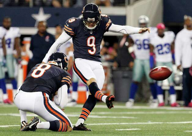 Chicago Bears punter Adam Podlesh (8) holds as kicker Robbie Gould (9) makes a field goal against the Chicago Bears during the first half of an NFL football game, Monday, Oct. 1, 2012 in Arlington, Texas. (AP Photo/Tony Gutierrez) Photo: Tony Gutierrez, Associated Press / AP