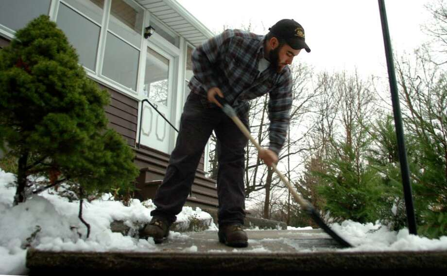 Nick Ellis, with Corchard Snowplowing, shovels the walkway in front of a house in Shelton Wednesday December 9, 2009 following the overnight snowfall. Photo: Autumn Driscoll / Connecticut Post