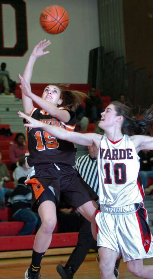 Stamford's Brittany Duffin is fouled by Fairfield Warde's Kate Kerrigan as she attempts a shot in the first half of Wednesday night's game at Warde. Photo: Autumn Driscoll / Connecticut Post