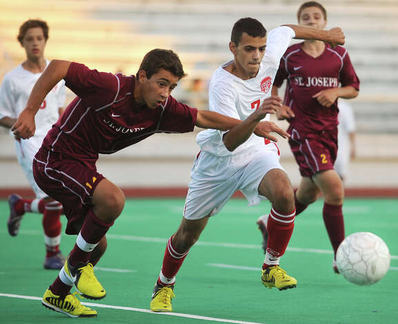 St. Joseph's Anthony Leonardi, left, and Central's Daniel Santos-Souza race for the ball during their matchup at Central High School in Bridgeport on Monday, October 1, 2012. Photo: Brian A. Pounds / Connecticut Post