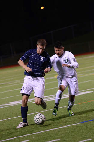 Staples' Ethan Bradeen (18) and Norwalk's Alejandro Rivera (7) battle for control of the ball during the boys soccer game at Norwalk High School's Testa Field on Monday, Oct. 1, 2012. Photo: Amy Mortensen / Connecticut Post Freelance
