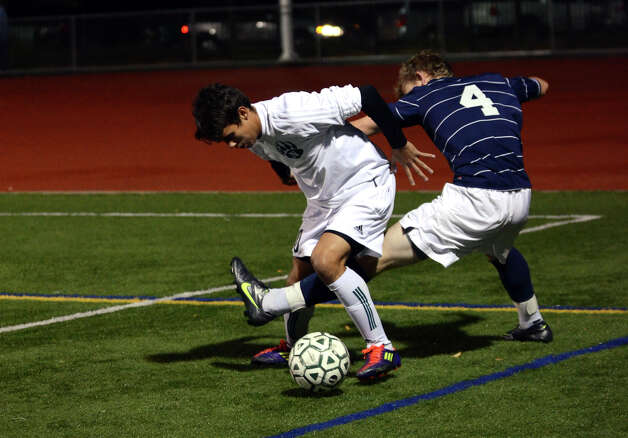 Staples' Harry Birch (4) gets tangled up with Norwalk's Nacho Navarro (20) as they battle for control of the ball during the boys soccer game at Norwalk High School's Testa Field on Monday, Oct. 1, 2012. Photo: Amy Mortensen / Connecticut Post Freelance