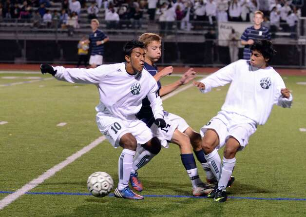 Staples' Jack Scott (14) collides with Norwalk's Santiago Muriel (10) and Jose Canahui (6) during the boys soccer game at Norwalk High School's Testa Field on Monday, Oct. 1, 2012. Photo: Amy Mortensen / Connecticut Post Freelance