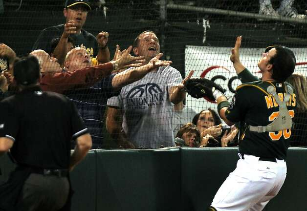 A's catcher Derek Norris and fans go after a foul ball in the seventh inning. Photo: Lance Iversen, The Chronicle