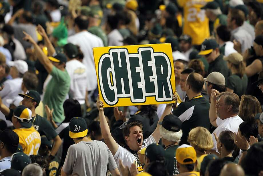 A fan tries to fire up his fellow green and gold supporters. Photo: Carlos Avila Gonzalez, The Chronicle