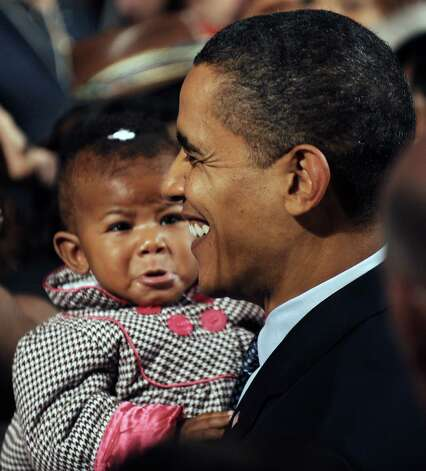 President Obama holds a baby after delivering remarks on the economy at Lehigh Carbon Community College in Allentown, Pa., on December 4, 2009. (NICHOLAS KAMM/AFP/Getty Images) Photo: NICHOLAS KAMM, Nicholas Kamm/Getty Images