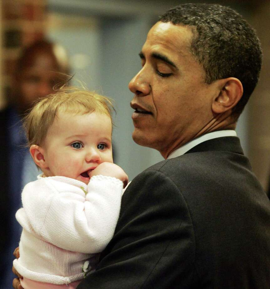 US Democratic presidential hopeful Illinois Senator Barack Obama holds a baby after holding an education roundtable discussion in Alexandria, Va., on Feb. 10, 2008. Photo: Saul Loeb/AFP/Getty Images