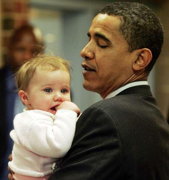 US Democratic presidential hopeful Illinois Senator Barack Obama holds a baby after holding an educa