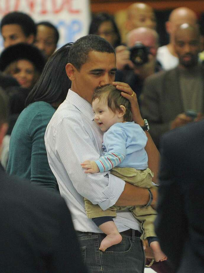 Barack Obama holds a baby as he visits volunteers during a National Day of Service Project event where volunteers were writing letters for troops on Jan. 19, 2009 at Coolidge Senior High School in Washington. Photo: MANDEL NGAN, Mandel Ngan/AFP/Getty Images