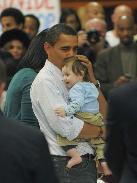 Barack Obama holds a baby as he visits volunteers during a National Day of Service Project event whe
