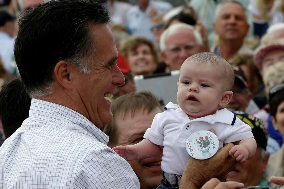 "Mitt Romney picks up a baby wearing a ""Dump Obama"" pin as he campaigns in Pueblo, Colo., Monday, Sept. 24. (AP Photo/Charles Dharapak) Photo: Charles Dharapak, Charles Dharapak/AP"