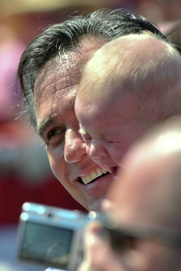 Mitt Romney holds a crying baby after speaking at a campaign rally in Fairfax, Va., on Sept. 13. NICHOLAS KAMM/AFP/GettyImages Photo: NICHOLAS KAMM, Nicholas Kamm/AFP/Getty Images