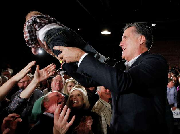 Mitt Romney hands a baby back to the audience as he campaigns at The Hall at Senate's End, in Columbia, S.C., Wednesday, Jan. 11. (AP Photo/Charles Dharapak) Photo: Charles Dharapak, Charles Dharapak/AP