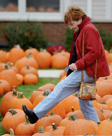 Helen Mooney of Albany steps carefully over the pumpkins at the McKownville Methodist Church in Albany, N.Y. October 1, 2012.    Profits from the sale of the pumpkins support the mission scholarships at the church.   (Skip Dickstein/Times Union) Photo: Skip Dickstein