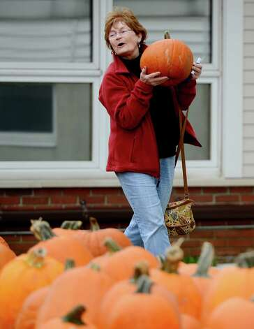 Helen Mooney of Albany carries her pumpkin to the check out at the McKownville Methodist Church in Albany, N.Y. October 1, 2012.    Profits from the sale of the pumpkins support the mission scholarships at the church.   (Skip Dickstein/Times Union) Photo: Skip Dickstein