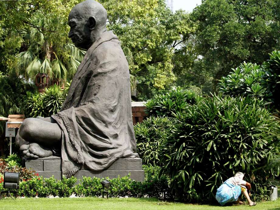 A gardener tends to plants near a statue of Mahatma Gandhi on his birth anniversary, at the Indian Parliament in New Delhi , India, Tuesday, Oct. 2, 2012. (AP Photo/ Mustafa Quraishi) Photo: Mustafa Quraishi, Associated Press / AP