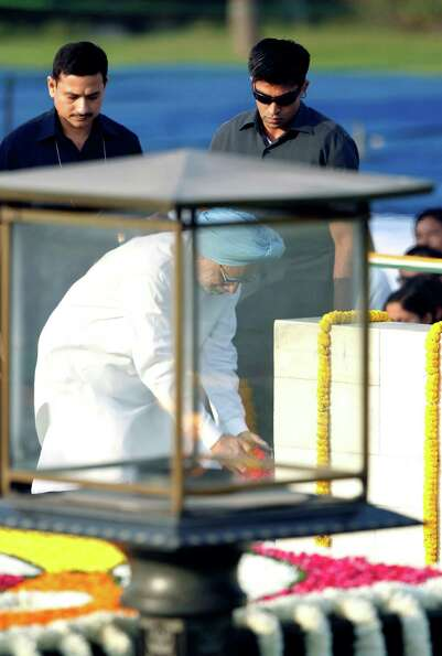 Indian Prime Minister Manmohan Singh pays floral tributes to the memorial of Mahatma Gandhi on his b
