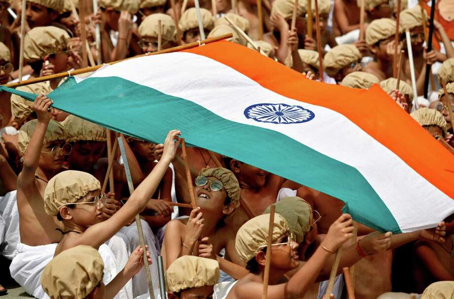 Indian school children, dressed as Mahatma Gandhi, carry an Indian flag while participating in an event to mark his birth anniversary in Chennai, India, Tuesday, Oct. 2, 2012. (AP Photo/Arun Sankar K.) Photo: Arun Sankar K., Associated Press / AP