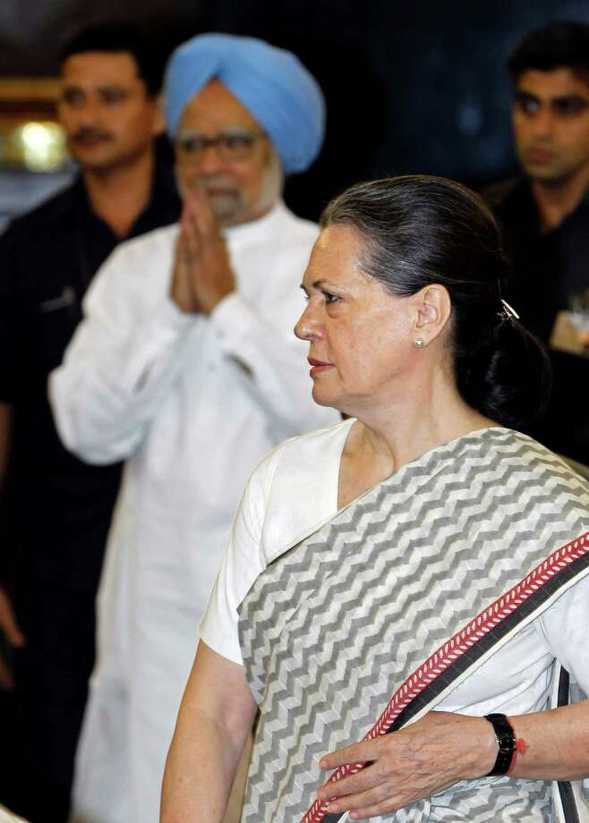 Congress Party President Sonia Gandhi, right, stands as Indian Prime Minister Manmohan Singh, center, arrives to pay tribute to Mahatma Gandhi on his birth anniversary, at the Indian parliament house in New Delhi , India, Tuesday, Oct. 2, 2012. (AP Photo/ Mustafa Quraishi) Photo: Mustafa Quraishi, Associated Press / AP