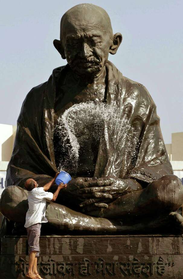 A man throws water on a statue of  Mahatma Gandhi as he cleans it up on the eve of his birth anniversary at Gujarat state legislature complex in Gandhinagar, Gujarat state, India, Monday, Oct. 1, 2012. (AP Photo/Ajit Solanki) Photo: Ajit Solanki, Associated Press / AP