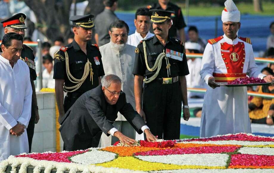 Indian President Pranab Mukherjee pays floral tributes to the memorial of Mahatma Gandhi on his birth anniversary in New Delhi , India, Tuesday, Oct. 2, 2012. (AP Photo/ Mustafa Quraishi) Photo: Mustafa Quraishi, Associated Press / AP