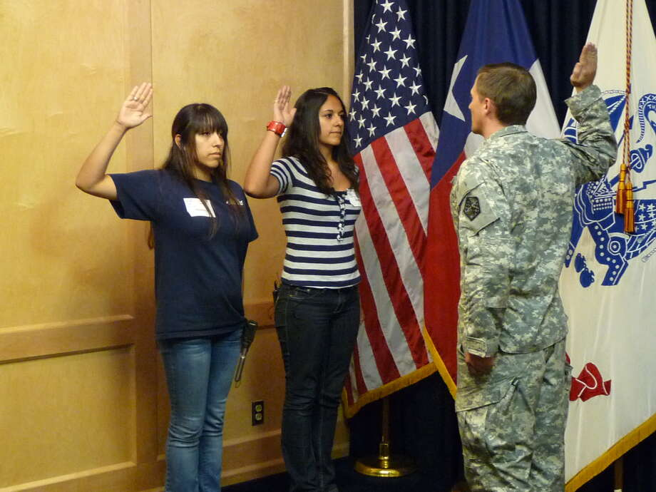 2011 Judson High School graduate Sarah Gomez, left, and her sister, Judson senior Meladee Gomez, are sworn in Sept. 13 as members of the Texas Army National Guard, with Capt. Mathews Metyko conducting the ceremony at Joint Base San Antonio-Fort Sam Houston. Photo: Photo Courtesy Of Judson ISD Pub