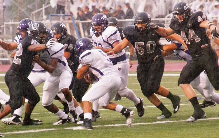 Steele Knight defenders cut through a driving rainstorm to bring down a San Marcos ball carrier during their 42-14 win Sept. 27 at Lehnhoff Stadium. Photo: Lavon Brown / For The NE Herald