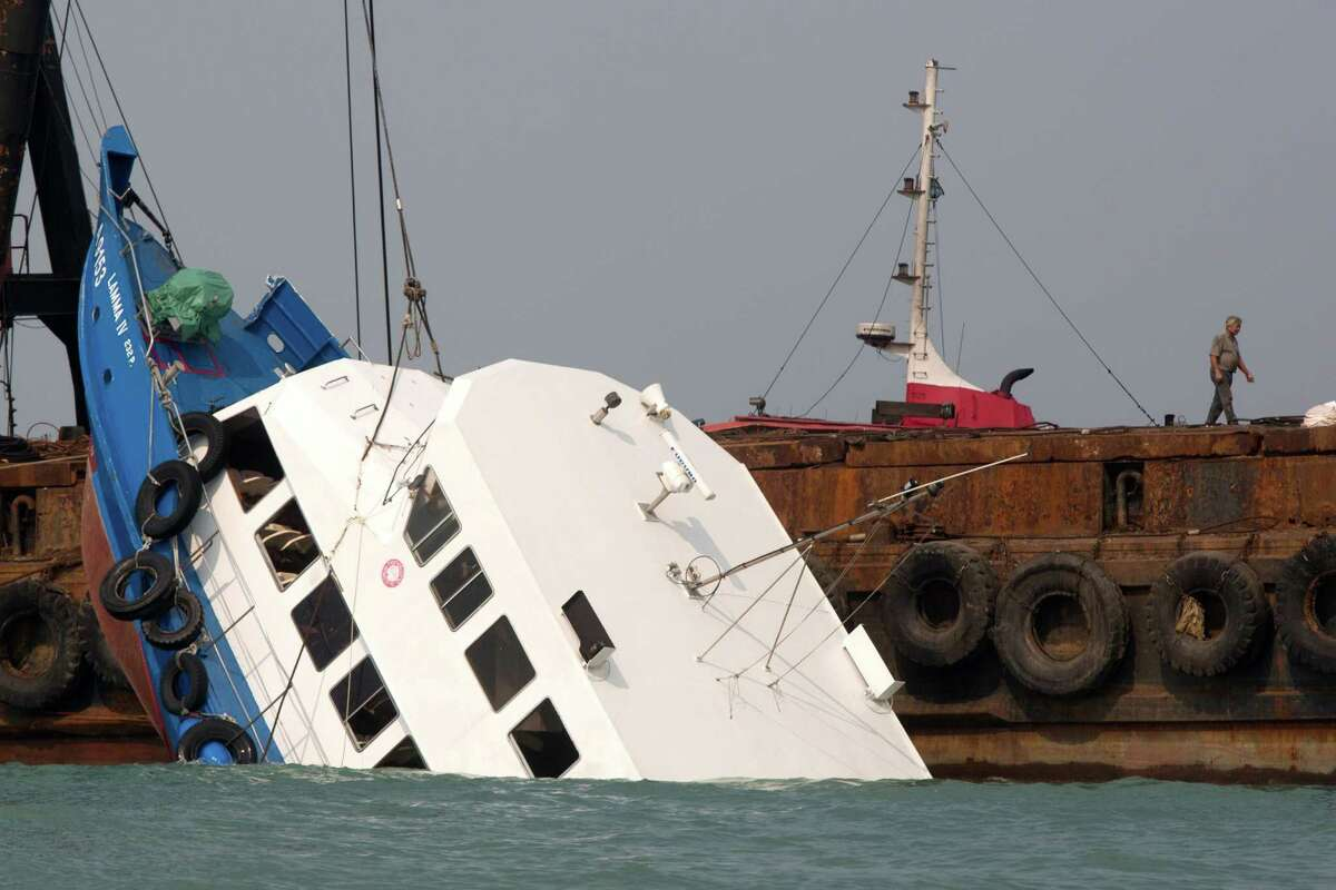 HONG KONG - OCTOBER 2: The stricken ferry is pulled out of the water near Yung Shue Wan on Lamma Island on October 2, 2012 in Hong Kong. Thirty-six passengers have been killed and several others were injured when a Hong Kong Electric ferry, carrying 124 people, collided with a tug boat off the coast of Hong Kong late on Monday.