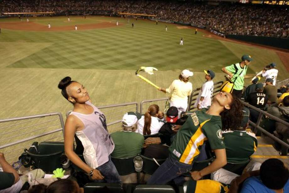 """Vanessa Fisher, right, and Breanna Britton, left, do """"The Bernie"""" during  a break in the action of the A's game against the Rangers at O.co  Coliseum in Oakland in 2012."""