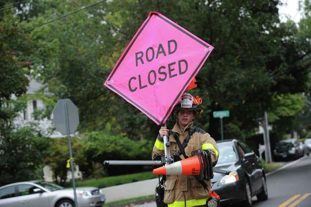 "Cos Cob Firefighter Brett Atkinson places a ""Road Closed"" sign on MacArthur Drive in Old Greenwich near the scene of a Havemeyer Lane fire that killed a 42-year-old man and seriously injured a woman Tuesday morning, Oct. 2, 2012. Photo: Helen Neafsey / Greenwich Time"