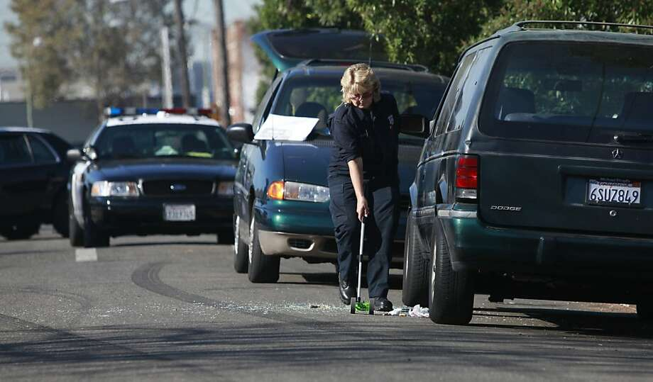 Oakland police gather evidence on the 1600 block of 72nd Avenue, where two men in a van were shot. Photo: Mike Kepka, The Chronicle