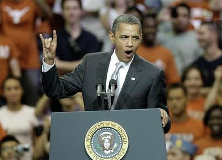"""President Barack Obama gives a """"hook 'em horns"""" sign as he starts a speech at Gregory Gym at the University of Texas in Austin, Texas, Monday, Aug. 9, 2010.   (AP Photo/LM Otero) (AP)"""
