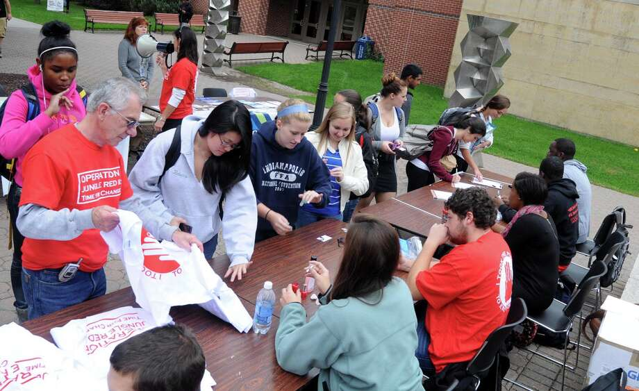 Students line up at the Operation Jungle Red ll table to sign a pledge to help end violence. Each participant's pinky nail was painted red, and each received a shirt at Western Connecticut State University's midtown campus on Tuesday, October 2, 2012. Photo: Lisa Weir