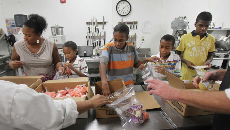 Veronica Parker packs after-school meals at the San Antonio Food Bank with her sons (left to right) 8-year-old Noah, 11-year-old Simeon, 10-year-old Nigel and 13-year-old Kendall. Photo: JOHN DAVENPORT, San Antonio Express-News / ©San Antonio Express-News/Photo Can Be Sold to the Public