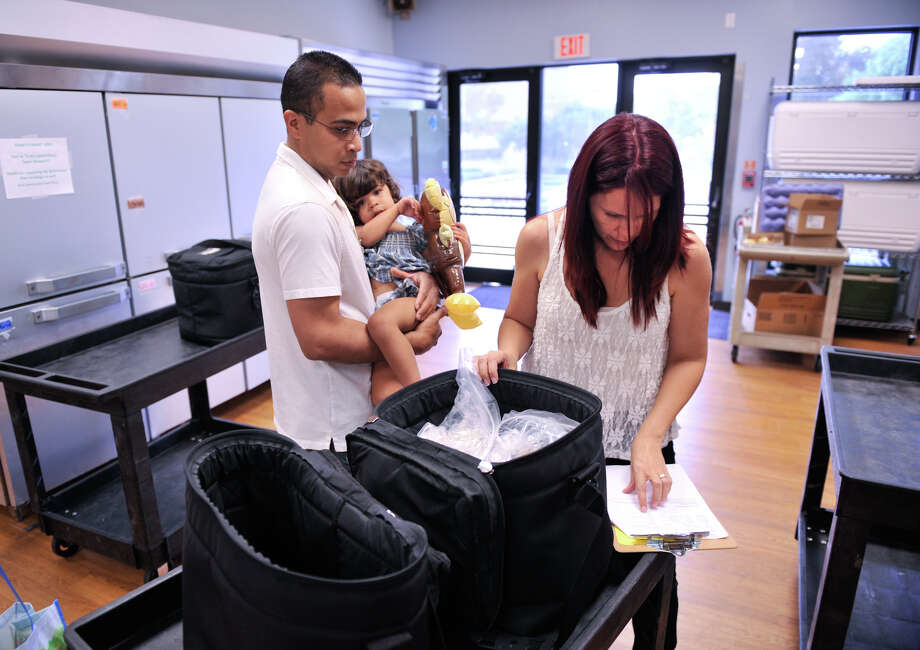Sharily Contreras and Miguel Escalera, along with daughter Anastasia, pack food in the Meals on Wheels kitchen. Photo: For The Express-News