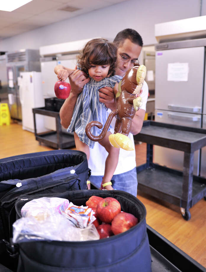 Miguel Escalera lifts daughter Anastasia as they prepare to pack their Meals on Wheels deliveries. Photo: For The Express-News