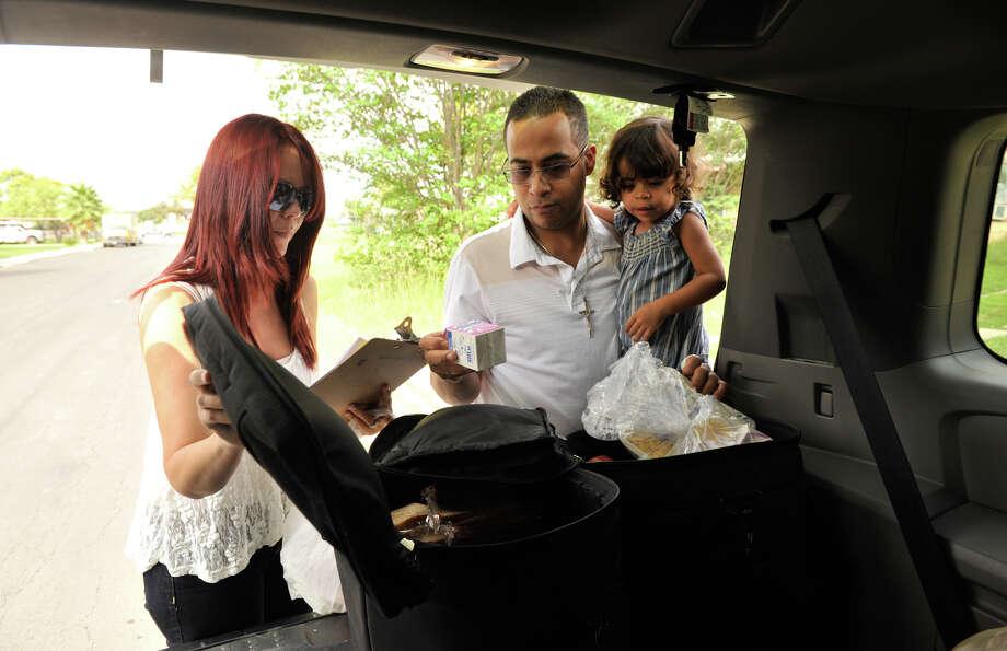 Sharily Contreras and Miguel Escalera carry out their Meals on Wheels route with 2-year-old daughter Anastasia. Photo: For The Express-News