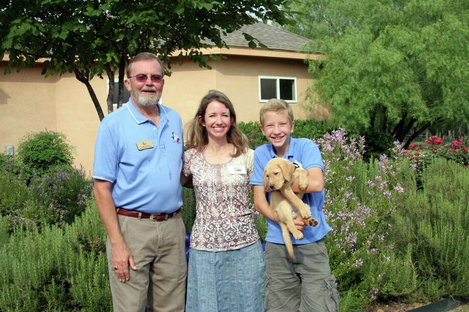 Amelia Gill and her son Daniel, 12, are raising a yellow Lab puppy to be a future guide dog for Guide Dogs of Texas. They pose with puppy program manager Larry Gelvin. Photo: Guide Dogs Of Texas