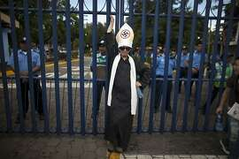 A man dressed as a Catholic priest with his hat covered by a Nazi swastika stands outside the National Police headquarters during a demonstration marking the Latin American Day for Decriminalization of Therapeutic Abortion in Managua, Nicaragua, Friday, Sept. 28, 2012. Abortion is illegal in Nicaragua.