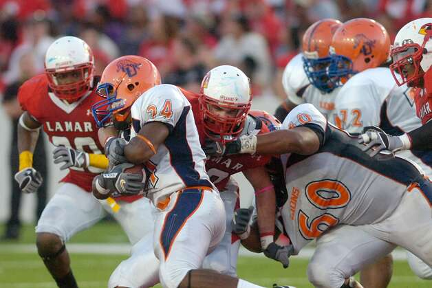 Lamar defensive tackle Mark Murrill, center, gets the stop on Langston University running back Ricky Shearin (24) during the first half at Provost Umphrey Stadium. Saturday, October 9, 2010 Valentino Mauricio/The Enterprise Photo: Valentino Mauricio / Beaumont