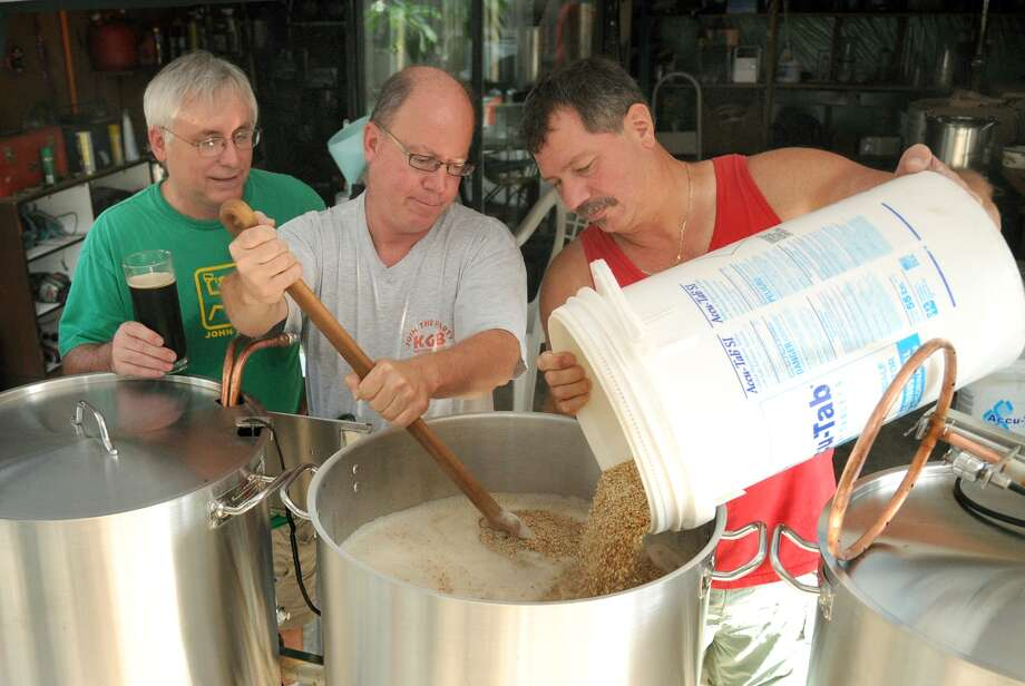 John Donaldson, from left, Wes Powell, and Ray Grella, all members of the Kuykendahl Gran Brewers, team up on the mashing and recirculating portion of a beer brewing session. Photo: Jerry Baker