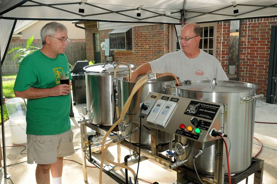 John Donaldson, from left, and Wes Powell, both members of the Kuykendahl Gran Brewers, team up during a beer-brewing session at Donaldson's home in Cypress. Photo: Jerry Baker