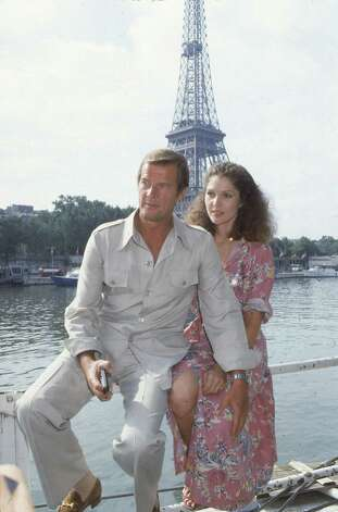 "1978: Moonraker — Co-stars Roger Moore, left, and Lois Chiles pose by the Eiffel Tower in Paris, France, Aug. 7, 1978, one week before filming begins for the 11th James Bond film, ""Moonraker.""  Chiles will play the part of Dr. Holly Goodhead. Photo: Associated Press / AP1978"
