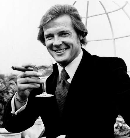 "1973: Live And Let Die — Actor Roger Moore poses with a martini and a cigar at the Dorchester Hotel in London, on August 1, 1972, after the announcement was made that he will play the British secret agent James Bond 007, in the new production ""Live and Let Die."" Photo: Associated Press / AP1972"