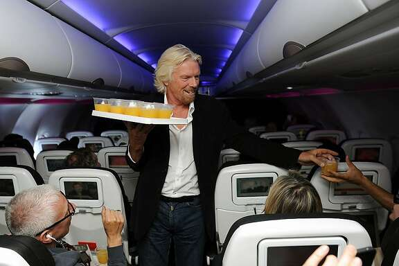 In this photo released by Virgin America Airlines, Virgin Group founder Richard Branson passes out beverages to guests aboard Flight 11 from New York to San Francisco, Wednesday, Sept. 19, 2012.  Branson invited frequent flyers to be part of Virgin America's new ad campaign by sharing their own photo moments from 35,000 feet via Instragram and Twitter. The photos were then transmitted in-flight via the airlines WiFi to live digital boards at Times Square in New York.  (AP Photo/Virgin America, Bob Riha, Jr.)