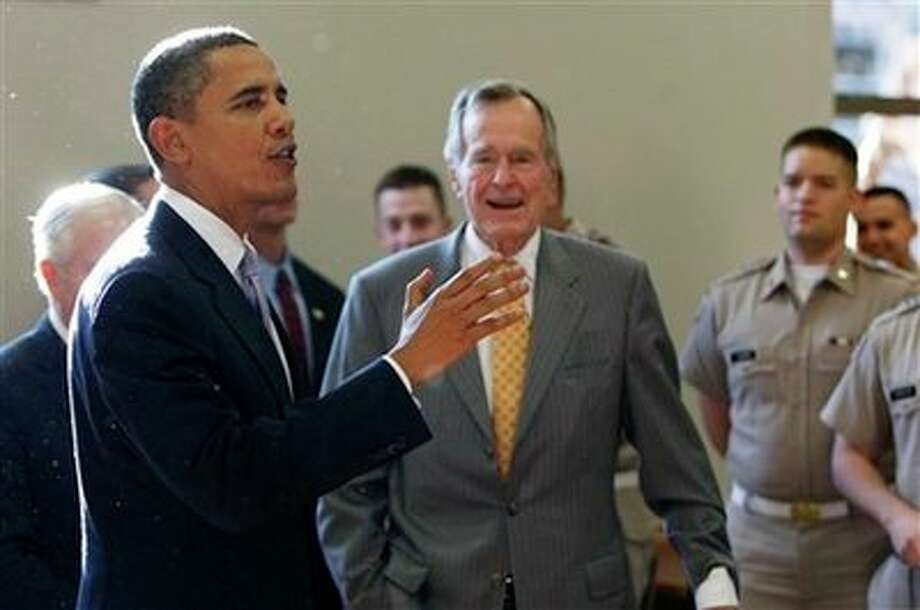 President Barack Obama and former President George H.W. Bush, right, talk with corp cadets in the cafeteria prior to the Points of Light Institute forum at Texas A&M University in College Station, Texas, Friday, Oct. 16, 2009. (AP Photo/Gerald Herbert) (AP)